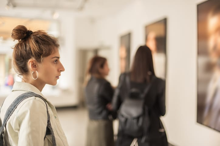 Group of woman looking at modern painting in art gallery. Abstract painting